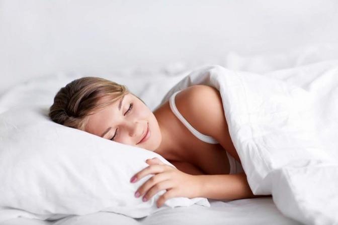 Eine Frau liegt schlafend in Seitenlage im Bett und träumt offensichtlich etwas Schönes, denn sie hat ein leichtes Lächeln im Gesicht.