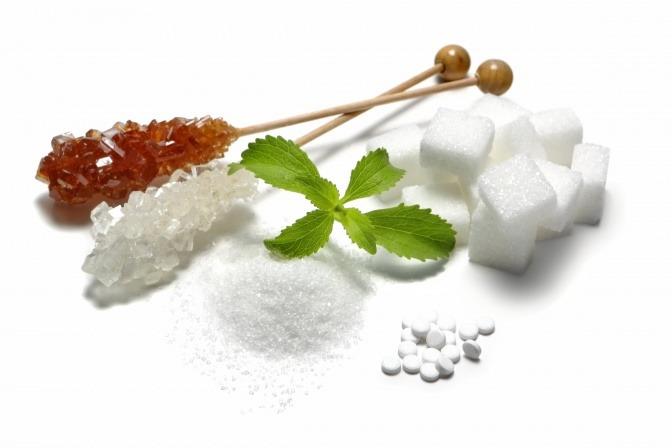 Verschiedener gesunder Zuckerersatz liegt neben einem Löffel Zucker