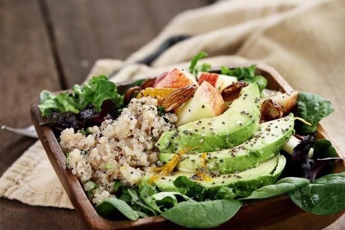 Eine Schüssel mit einem gemischten Salat, der unter anderem Quinoa, Avocado, und diverse Kräuter enthält.
