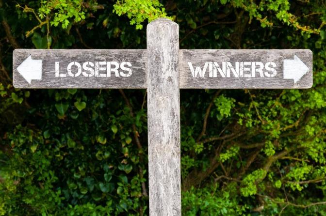Auf Wegzeigern stehen die Worte Gewinner und Verlierer