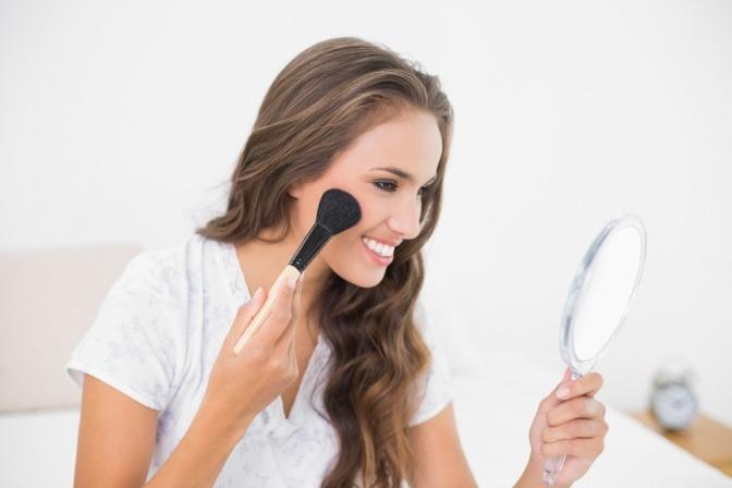 Frau schminkt schimmernde Haut