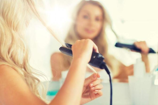 Frau bekommt mit Glätteisen Locken ins Haar