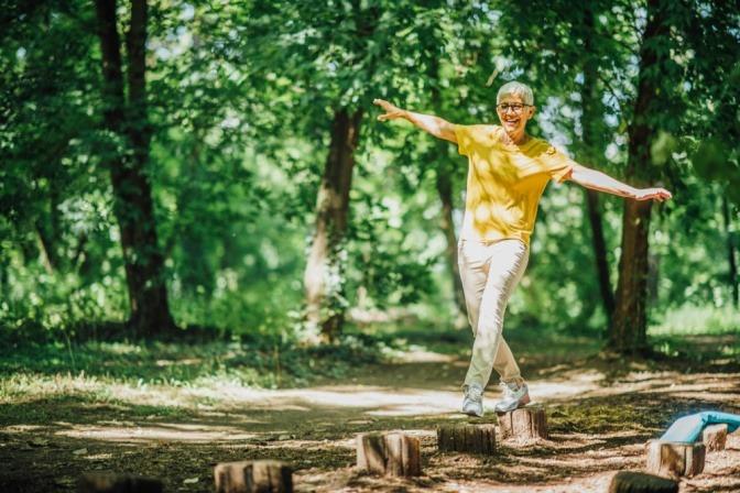 Eine ältere Frau balanciert auf abgesägte Baumstämmen