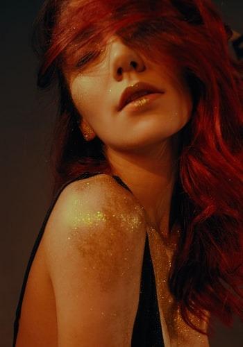 Eine rothaarige Frau trägt im Gesicht und am Körper goldenen Glitter