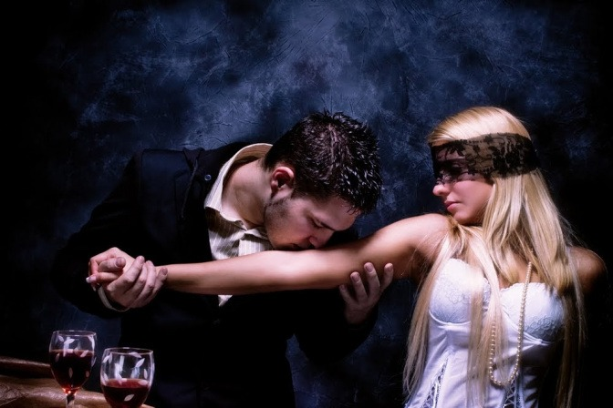 Ein festlich gekleidetes Pärchen sitzt gemeinsam am Tisch, sie hat die Augen verbunden, während er ihren ausgestreckten Arm liebkost.