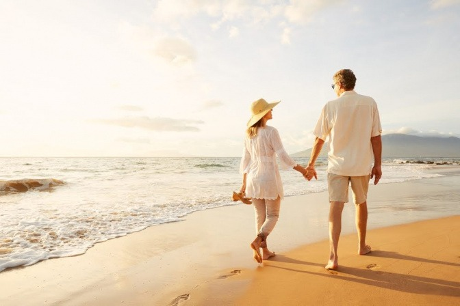 Ein Paar geht Hand in Hand am Strand spazieren.