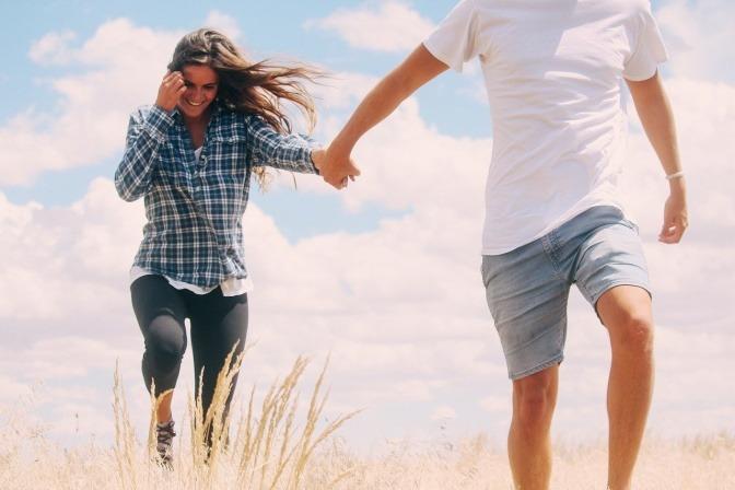 Ein Paar läuft glücklich über eine Wiese