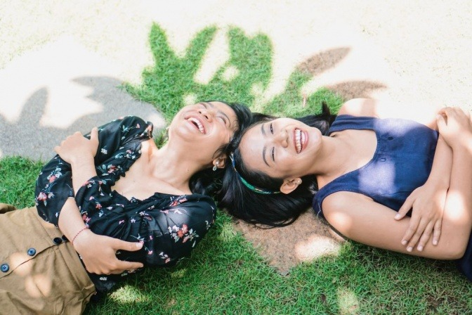 Zwei Freundinnen liegen glücklich am Boden