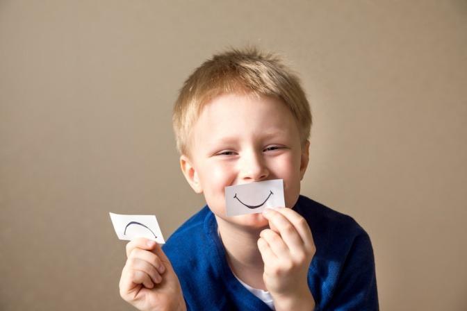 Ein Junge tauscht einen Zettel mit einem traurigen Mund gegen einen fröhlichen Mund aus