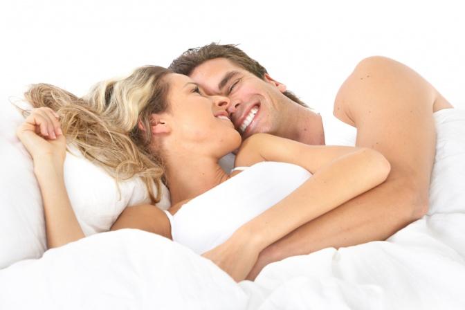 Ein Paar liegt glücklich im Bett