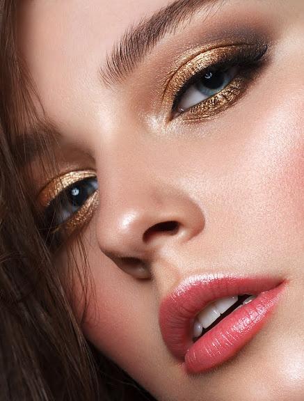 Eine Frau trägt ein gold schimmerndes Augen-Makeup
