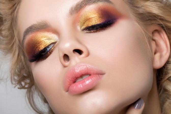 Eine Frau trägt ein buntes Augen Make-up in verschiedenen Wasserfarben