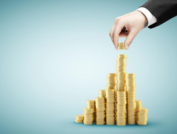 Eine Hand stapelt goldene Münzen zu einem Turm aufeinander