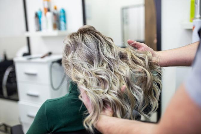 Eine Frau bekommt den Haarfarbentrend Grey Blending