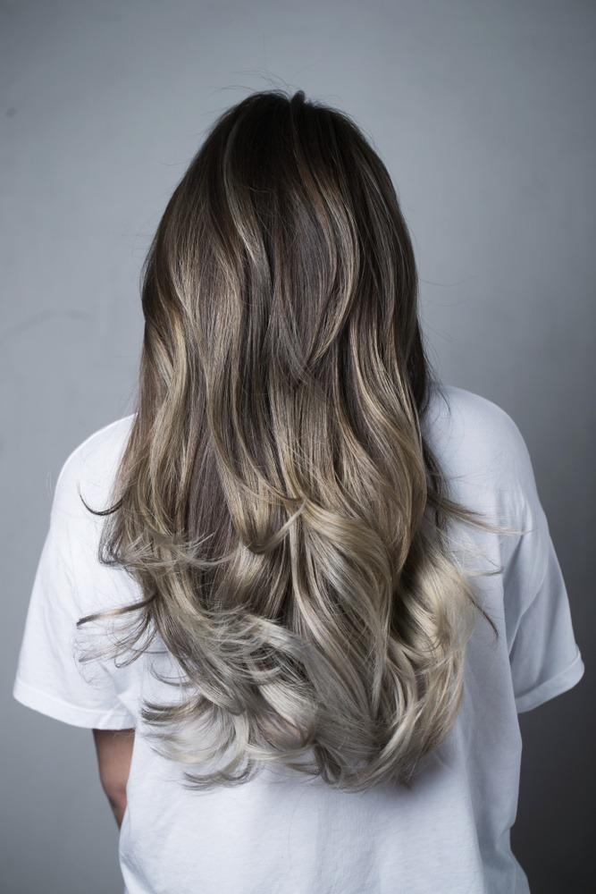 Eine Frau mit langen, silbergrau gesträhnten Haaren steht mit dem Rücken zur Kamera