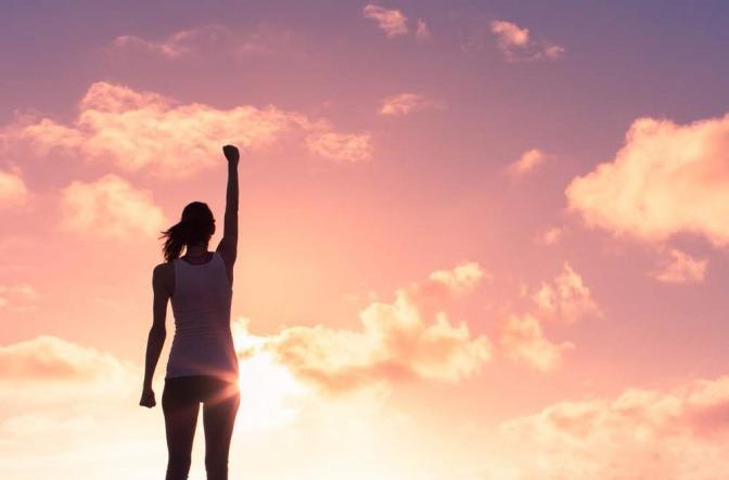 Eine Frau streckt selbstbewusst einen Arm nach oben