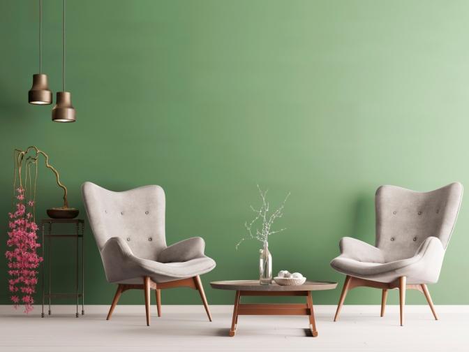 Vor einer grünen Wand stehen zwei Stühle und ein Tisch