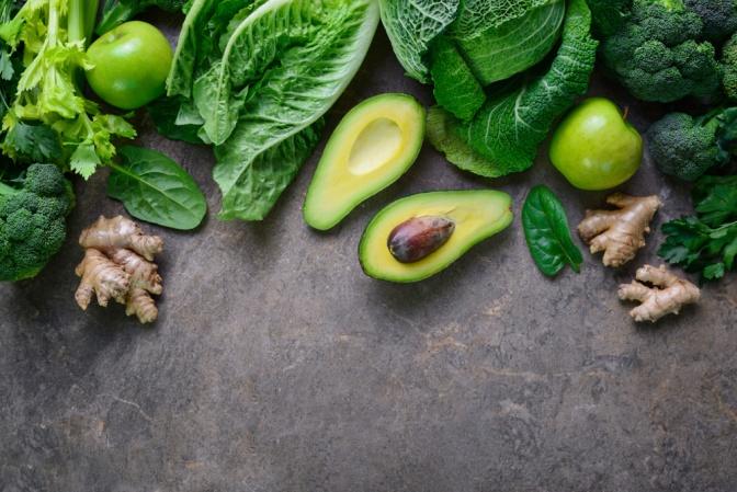 Advocado, Broccoli, Kohl, grüne Äpfel und Ingwer am Tisch arrangiert