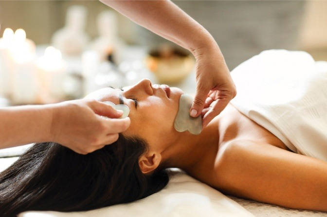 Eine Gua Sha Massage mit Jadesteinen im Gesicht