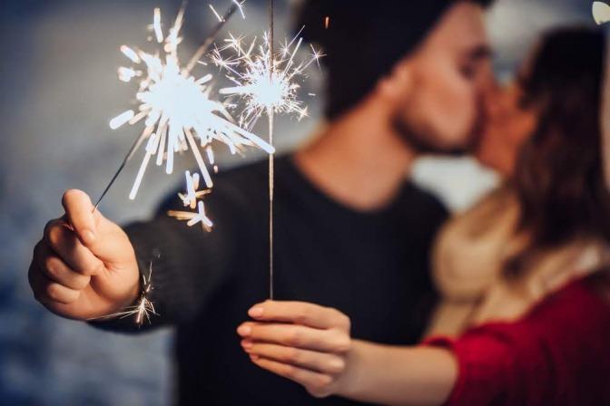 Ein Pärchen küsst sich, während jeder Partner in einem ausgestreckten Arm eine brennende Wunderkerze festhält.