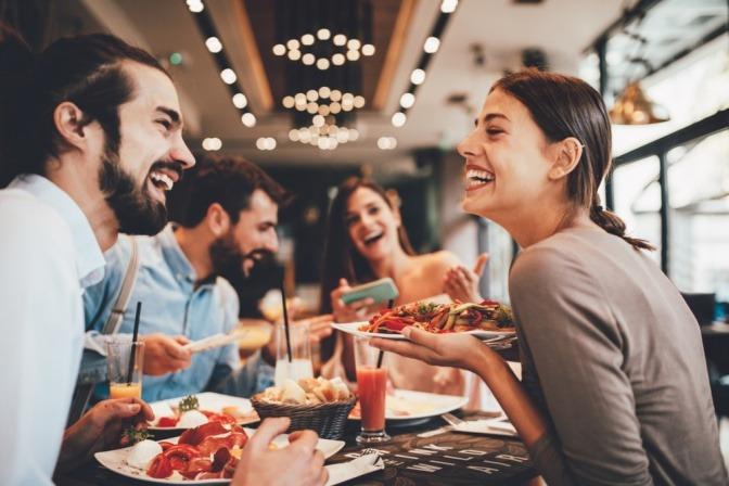 Vier Freunde essen in einem Restaurant und lachen dabei