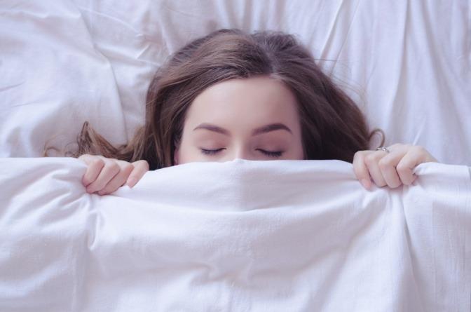 Eine Frau mit gutem Schaf unter einer Bettdecke