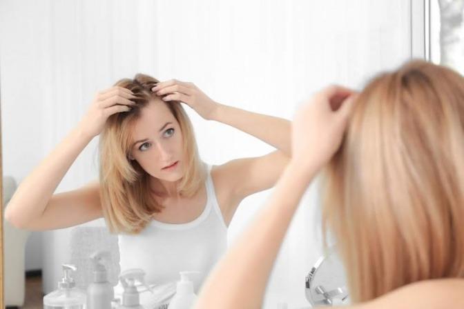 Eine blonde Frau betrachtet ihren dunklen Haaransatz