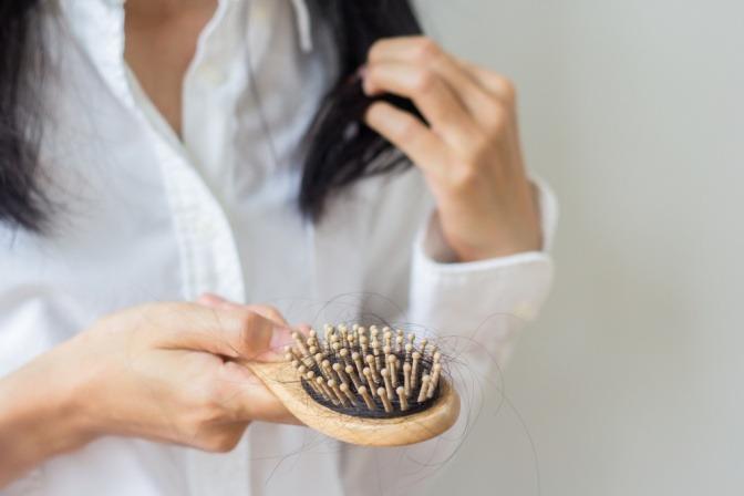 Frau betrachtet Bürste nach dem Bürsten ihrer langen Haare