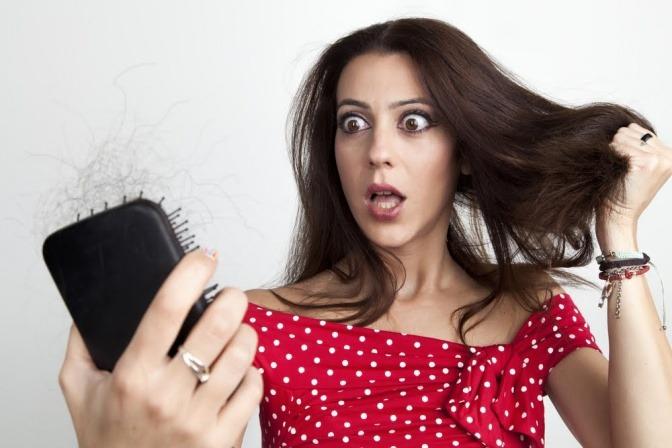 Eine Frau betrachtet erschrocken die Haare in der Bürste