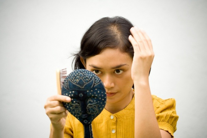 Frau untersucht Haare vor Handspiegel
