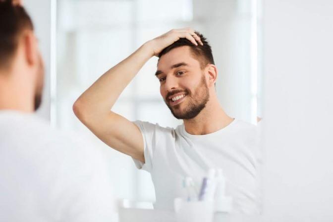 Ein Mann freut sich über seine schönen Haare