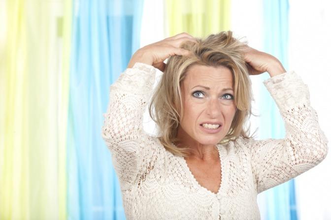 Eine Frau mit Haarausfall in den Wechseljahren rauft sich die Haare