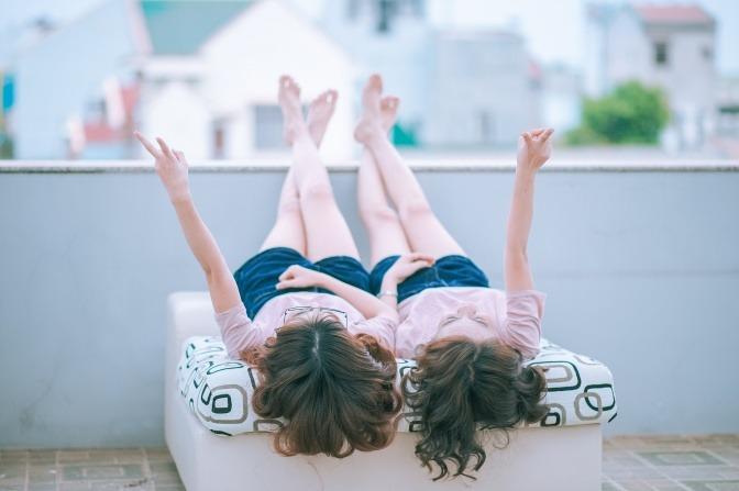 Zwei Frauen mit langen Haaren liegen nebeneinander.