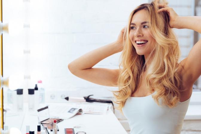 Eine Frau massiert die Kopfhaut, um Haarausfall vorzubeugen