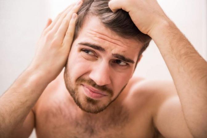 Mann betrachtet seine Haare kritisch vor dem Spiegel.