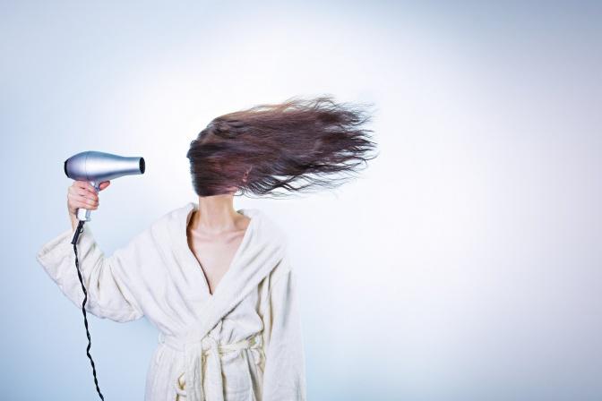 Eine Frau ist beim Haare föhnen