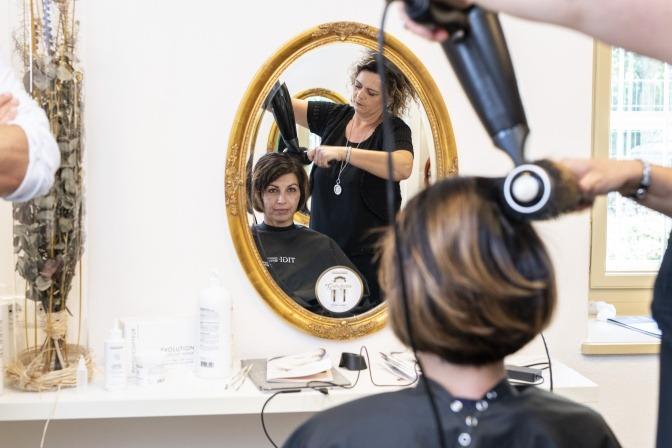 Frau bekommt Haare geföhnt im Zuge einer Kopfhautsanierung