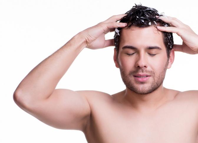 Ein Mann massiert eine Haartinktur ein