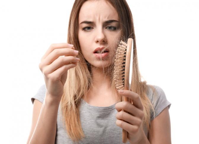 Frau pflückt Haare aus Bürste.