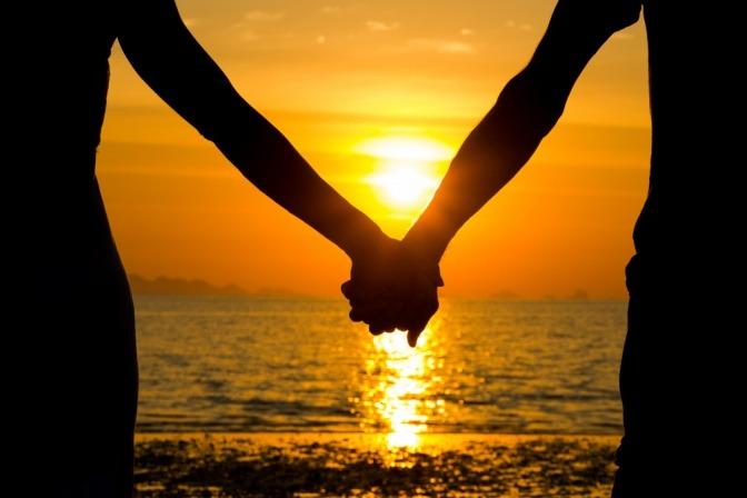 Ein Paar hält am Strand Händchen und beobachtet den Sonnenuntergang.