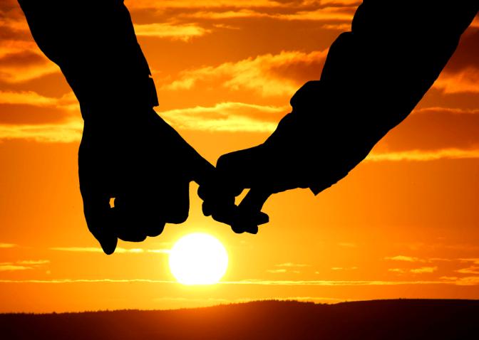 Zwei Hände halten sich bei Sonnenuntergang