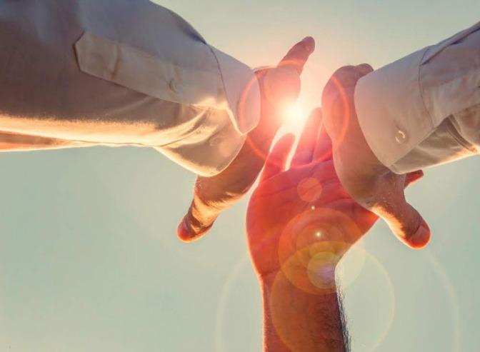 Drei Menschen reichen einander die Hände