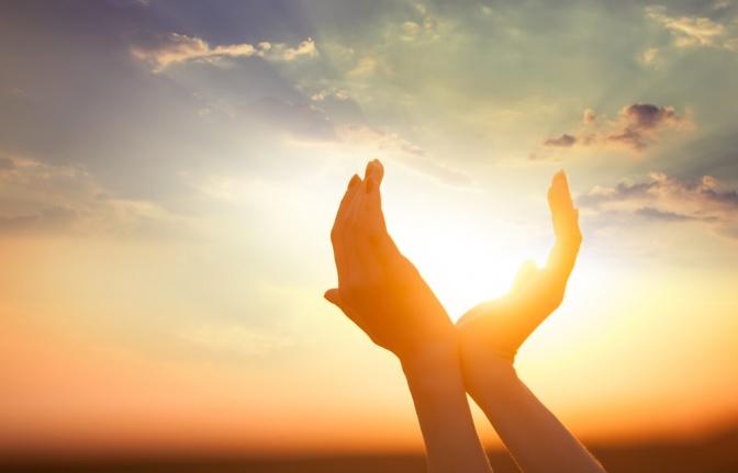 Zwei Hände halten die Sonne fest