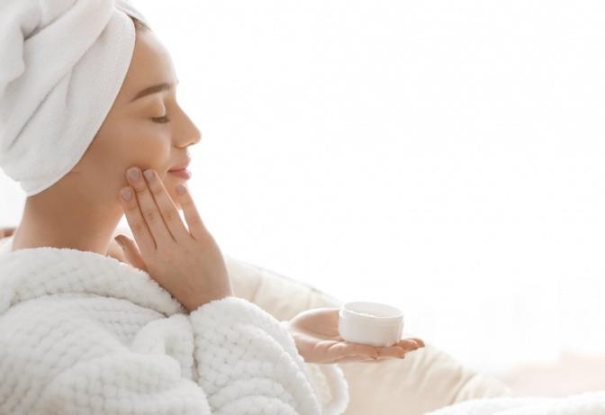 Frau im Bademantel cremt ihr Gesicht ein