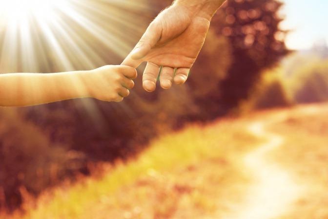 Die Hand eines Kindes reicht zu einer Hand eines Erwachsenen