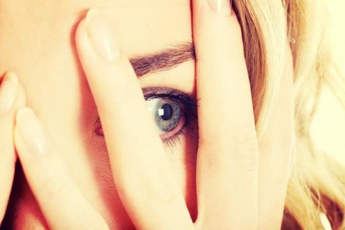 Eine Frau hält ihre Hand vor ihr Auge