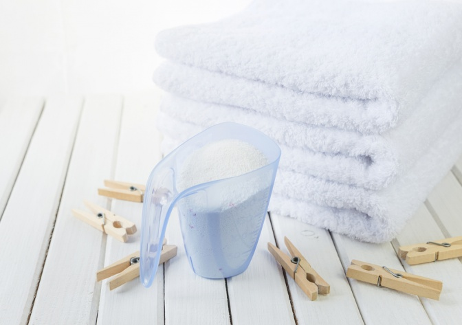 Ein Stapel Frotteehandtücher mit Wäscheklammern und Waschmittel