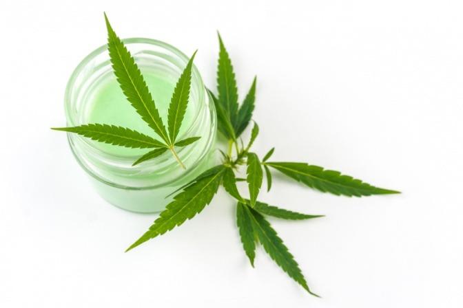 Cremetiegel und Cannabis-Blätter für Hautpflege bei Schuppenflechte