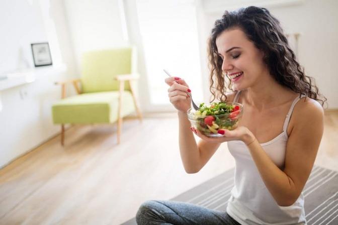Eine Frau isst Salat mit Hanföl