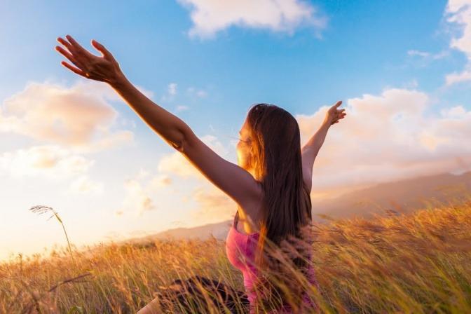 Eine Frau blickt in den Sonnenuntergang und breitet die Arme aus. Es wirkt, als wollte sie die positive Energie dieses schönen Anblicks einfangen.